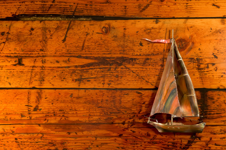 vibrant color: Copper sailboat set against a highly textured wood background.  Vibrant color, texture, and lighting with copy space on left.