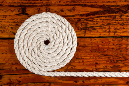 coiled rope: Coiled white rope on a highly textured wooden background.  Nautically themed studio close-up. Stock Photo