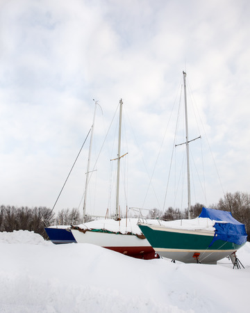 michigan snow: Three sailboats side by side in the snow.  Stored on land for winter.  Waiting for Spring. Copy space.