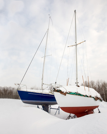 michigan snow: Two sailboats side by side in the snow.  Stored on land for winter.  Waiting for Spring.
