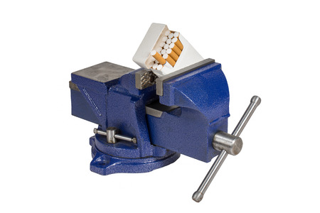 vice grip: Pack of cigarettes held in a blue vise grip.  Isolated on white.  Concepts could include vice in a vise, dealing with a crushing addiction, trapped by health issues, or others.