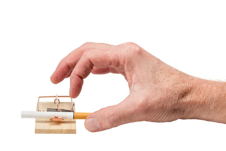 Handing reaching for cigarette in a mousetrap.  Studio closeup isolated on white background.
