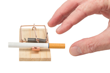 risking: Handing reaching for cigarette in a mousetrap.  Studio closeup isolated on white background.