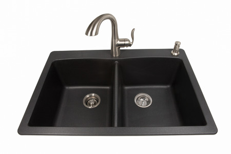 Modern kitchen sink made of black synthetic granite with brushed stainless steel faucet and soap dispenser.  Isolated on a white background.  Viewed from front.  Contemporary living and design.