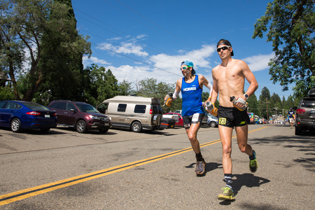 Ultra-marathon runner Paul Terranova in blue shirt and his pacer running in the Western States 100-mile Endurance Run.  Western States is one of the oldest and most popular ultra-marathons in the United States.  Editorial Use Only.