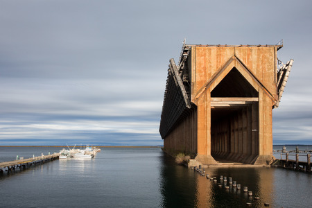 marquette: Abandoned ore dock once used to transfer coal and other materials between railroad cars and Lake Superior ore boats.  Interesting geometric structure captured near sunset with copy space and smaller boats for scale.