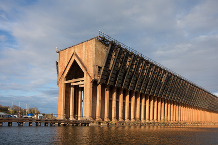 Abandoned ore dock once used to transfer coal and other materials between railroad cars and Lake Superior ore boats.  Interesting geometric structure captured near sunset.  Warm light and a dramatic sky.