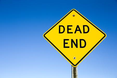 dead end: Photograph of a yellow Dead End sign shot against a clear blue sky.  Sign is mounted on a wooden post. Stock Photo