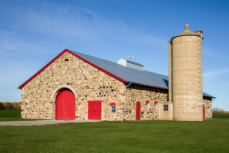 barn doors: Retro field stone barn with bright red doors set against a blue sky.  Vibrant colors and texture.