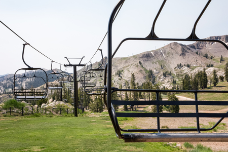 squaw: Empty ski lift chairs sitting idle during the summer season.  Selective focus on the foreground chair.  Rugged ski hill in the background.  Waiting for snow at Squaw Valley, a famous western USA ski resort.