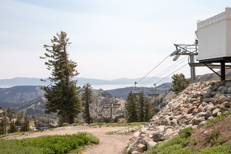 squaw: Ski lift engine sitting idle during summer season.  Shot at Squaw Valley.  Lake Tahoe and surrounding mountains are seen on the horizon.  Copy space in sky if needed.