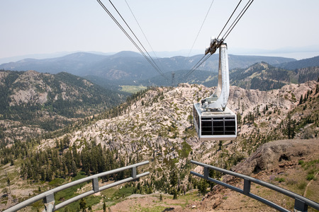 squaw: Dramatic view of a hanging gondola.  The tram is approaching the mountain top at Squaw Valley, a western USA ski resort seen here in summer.