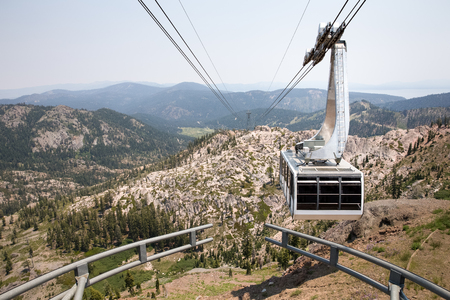 western usa: Dramatic view of a hanging gondola.  The tram is approaching the mountain top at Squaw Valley, a western USA ski resort seen here in summer.
