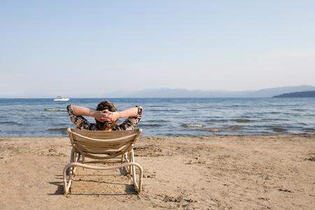 mujer mirando el horizonte: Relajado mujer sentada en una silla en la playa con las manos entrelazadas detrás de la cabeza. Mirando el horizonte como un barco cruza su punto de vista. Fotografiado en el lago Tahoe. Enfoque selectivo en primer plano. Copiar el espacio en el cielo.