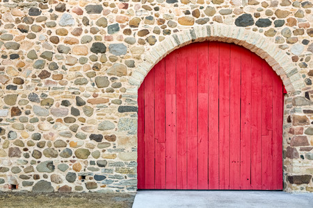 craftsmanship: Bright red arched door set in an old field stone wall.  Lots of texture, color, and craftsmanship.