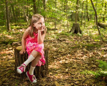 dappled: Young girl sitting on a stump in the forest, smiling and looking towards right side of frame and light.  Soft focus on background to allow for copy.  Dappled light coming through the trees for a soft, vintage feel. Stock Photo
