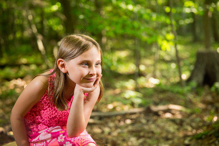 dappled: Young girl in forest, smiling and looking towards right side of frame and light.  Soft focus on background to allow for copy.  Dappled light coming through the trees for a soft, vintage feel.