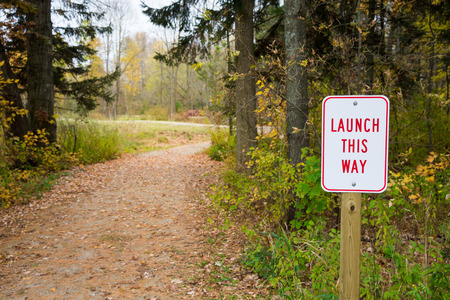 Launch This Way sign next to winding path leading into trees.  Soft focus on background to allow for copy.  Applicable concepts could include Product Launch, Beginnings, Exploration, or others.
