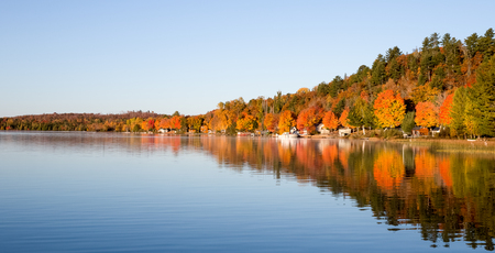 room for copy: Brilliant fall colors reflected in a smooth, calm lake photographed in morning light.  Room for copy on water or in sky if needed.
