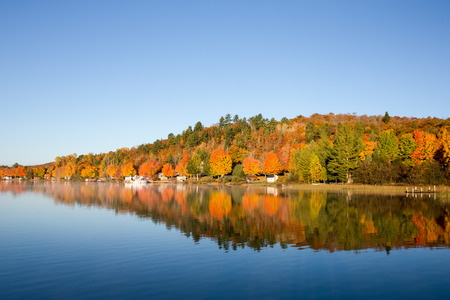 brilliant colors: Brilliant fall colors reflected in a glassy, smooth, blue lake.  Copy space on water and in sky if needed. Stock Photo