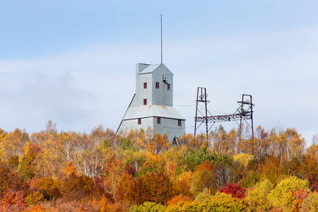 industrial park: Abandoned mine shaft house and other industrial structure on a hill and behind a cluster of trees in brilliant autumn colors.  Remnants of an abandoned copper mine that is now part of a Historic National Park in Upper Michigan.  Copy space in upper frame. Stock Photo