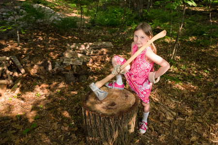 dappled: Young girl holding an ax while standing next to a stump or chopping block in the forest, looking confidently at the camera with one hand on her hip.  Dappled light and a high angle view add interest.  Unique image. Stock Photo