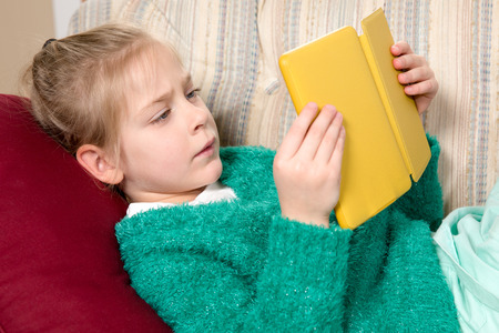 Young girl in a sweater reading a tablet while reclining on a couch.  Her serious expression indicates that she's engaged with the device and concentrating on what shes reading.