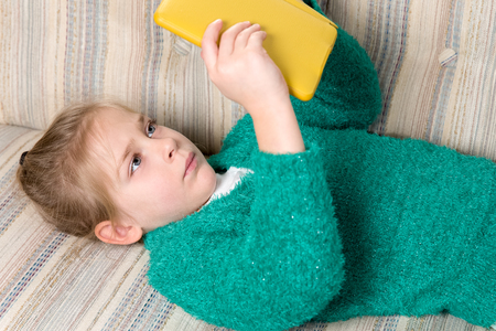 Young girl in a sweater reading a tablet while reclining on a couch.  Her serious expression indicates that she's engaged with the device and concentrating on what shes reading. Banco de Imagens