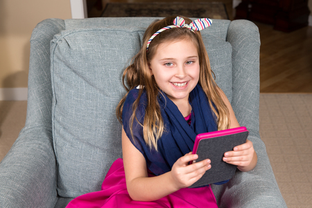 Young girl in a pink dress with an e-book reader or tablet.  The girl is smiling as she looks up from the device.  The tablet is color coordinated with her outfit.
