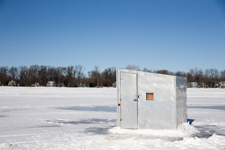 shanty: A lone ice shanty sitting on a frozen lake.  Copy space in the sky.  Photograph taken on Lake Winnebago, Wisconsin.  Concepts could include fishing, winter, nature, solitude, and others. Stock Photo