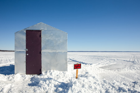 Ice shanty sitting on a frozen lake with a Keep Off The Grass sign juxtaposed against the barren landscape.  Copy space in the sky.  Concepts could include fishing, humor, nature, solitude, and others.