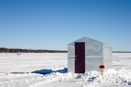 juxtaposition: Ice shanty sitting on a frozen lake with a Keep Off The Grass sign juxtaposed against the barren landscape.  Copy space in the sky.  Concepts could include fishing, humor, nature, solitude, and others.