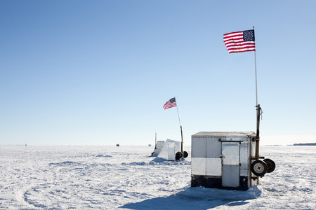 the backlighting: Ice shanties on a frozen lake flying American flags.  Backlighting highlights the starkness of the barren landscape.  Copy space in the sky.  Concepts could include fishing, patriotism, culture, nature, and others.