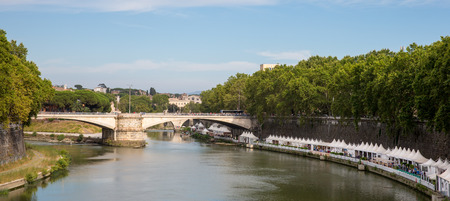 tevere: Panoramic view of the Tiber River Fiume Tevere in Rome.  Looking south from the Ponte Sisto bridge and showing restaurants and vendor shops along the rivers edge.