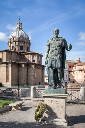 spqr: Julius Caesar statue with a wreath at its base and chapel dome and blue sky in the background.  Located near the Roman Forum and Colosseum.  Concepts could include history, leadership, art, and others.