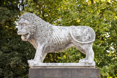 atop: Ancient stone lion statue in Tuscany, standing atop the medieval wall that surrounds the village of Lucca, Italy. Stock Photo
