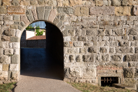 arched: Arched doorway in a medieval stone wall leading to the Tuscan village of Lucca, Italy.