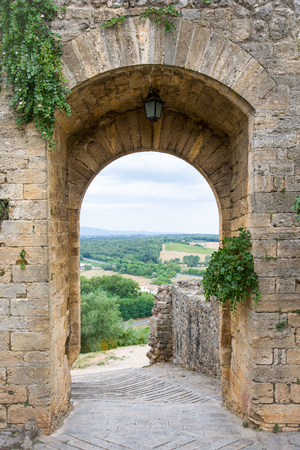 Arched doorway in a medieval stone wall in the Tuscan village of Monteriggioni, Italy.  Concepts could include travel, architecture, European heritage, others. Stock Photo