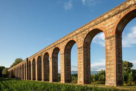Section of the Nottolini Aqueduct in Tuscany near Lucca, Italy.  Warm evening light with classic Tuscan textures and tones.  Concepts could include Travel, Architecture, Europe, others. Stock Photo