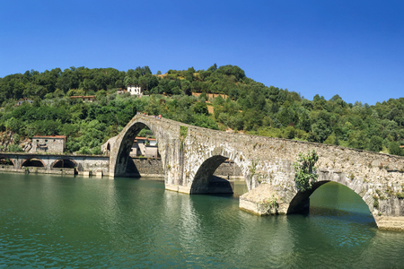 Ancient stone bridge, the medieval Ponte Maddalena, or Devils Bridge, in Tuscany.  Unrecognizable people at the crest of the bridge are included for scale.