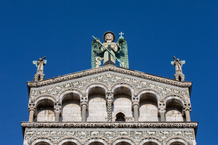 eyes looking down: Statue of St. Michael the Archangel perched atop the Church of San Michele in the Tuscan village of Lucca, Italy.  Sculpture has blue eyes and wings.  The ornate facade dates to the 13th century.