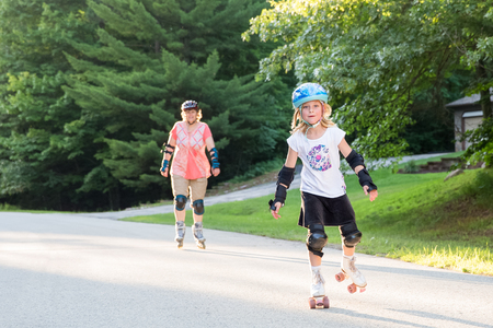 overseen: Happy, young girl on roller skates wearing safety gear, skating toward viewer, smiling, and looking into camera.  Overseen by woman in background who is in soft focus and warm light. Stock Photo