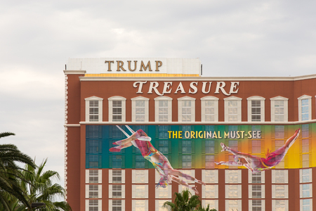 trapeze: Las Vegas, USA - October 28, 2016:  Trump International hotel marquee positioned behind the Treasure Island hotel as seen from the Vegas Strip in Las Vegas, NV.  The signage aligns to create a humorous message about Donald Trumps treasure.