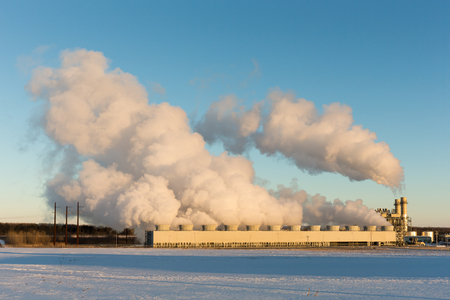 converts: Public power plant billows steam into the clear, blue, winter sky as it converts natural gas to electricity.  Snow on the ground.  Copy space in the sky if needed.