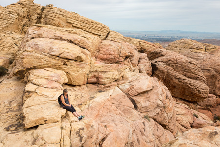 Confident female hiker taking in the view from a rocky mountain top in Red Rock Canyon National Conservation Area near Las Vegas, Nevada.  Concepts could include achievement, healthy lifestyle, freedom, others.