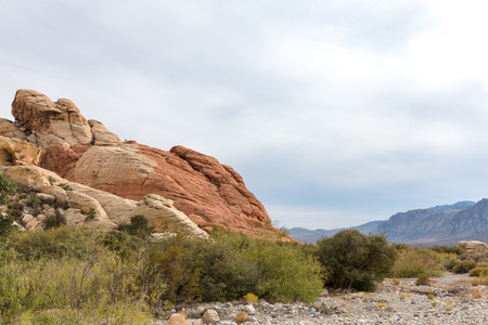 Large red rocks protruding from the desert floor at Red Rock Canyon National Conservation Area near Las Vegas, Nevada.  A mountain ridge in the distance with copy space in the sky if needed.