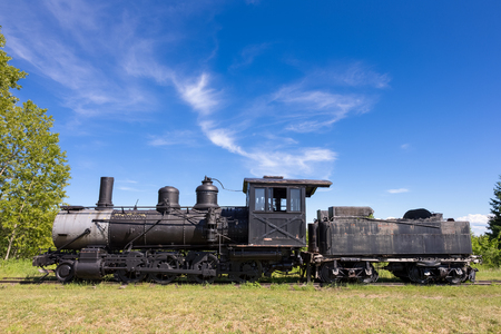 Dramatic view of an old steam train engine.  Abandoned locomotive and coal car seen on the prairie with copy space in blue sky if needed. Stock Photo
