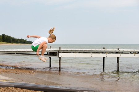 Girl jumping over water at a lakeshore.  Copy space in sky if needed.  Concepts could include childhood, play, joy, vacation, or many others.