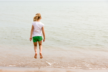Girl jumping over water at a lakeshore.  Viewed from behind with copy space if needed.  Concepts could include childhood, play, joy, vacation, or many others. Stock Photo