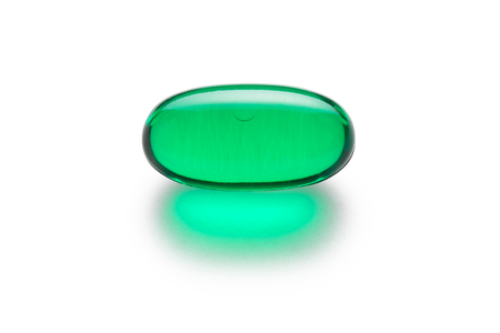 Green gelatin capsule or pill isolated on a white background.  Medically themed studio macro with backlighting for extra pop. Imagens